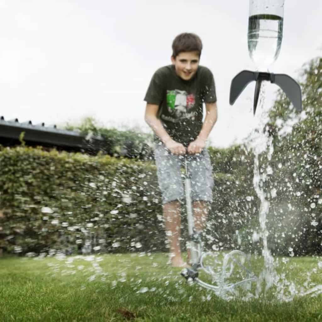 Boy playing outside with a 4M water rocket