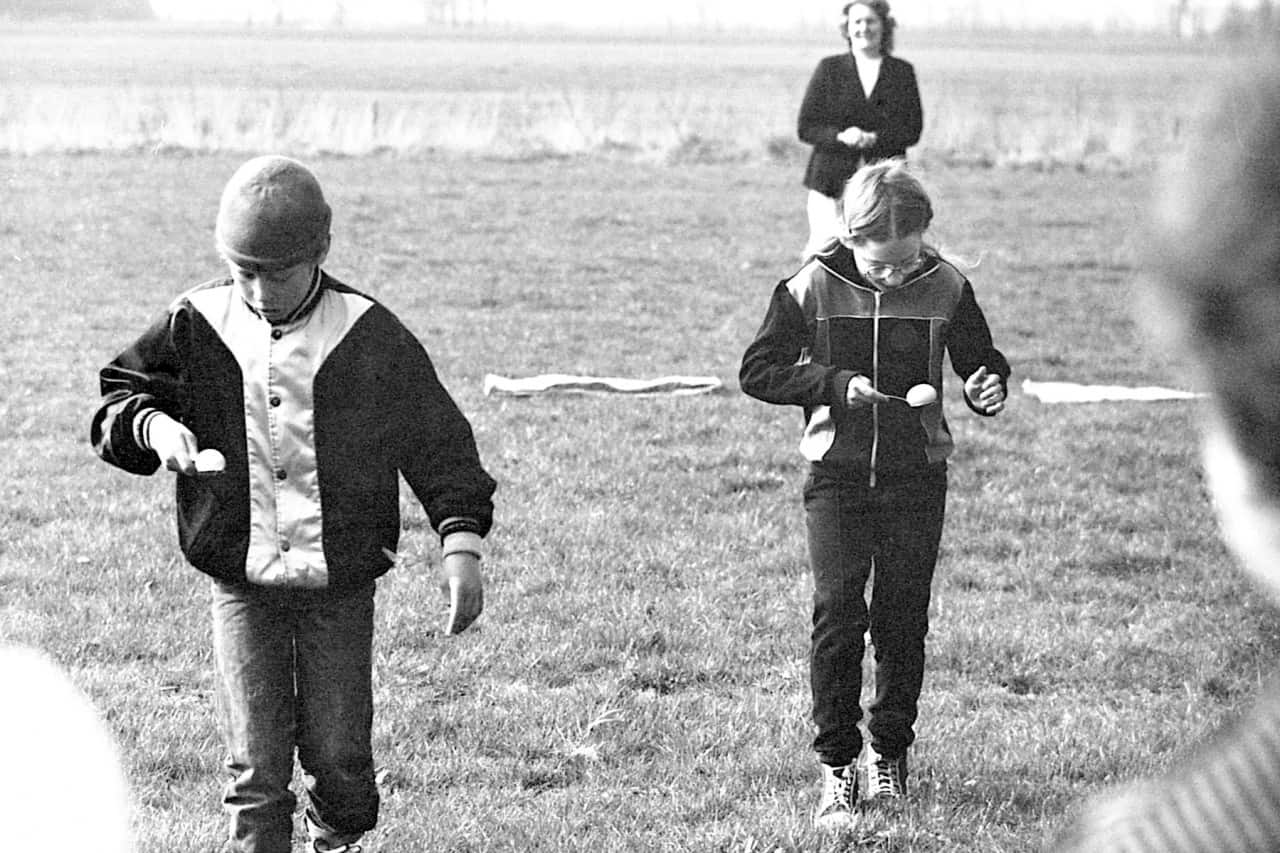 Old photo of two boys walking eggs