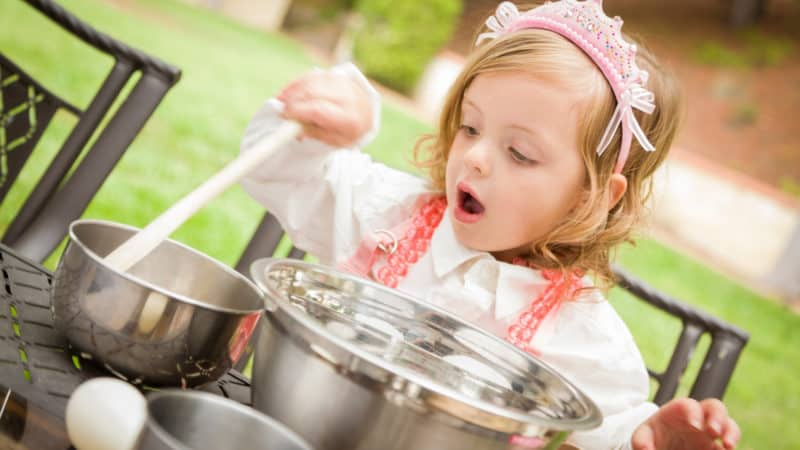 Little girl plays with pots and pans just like mom and dad