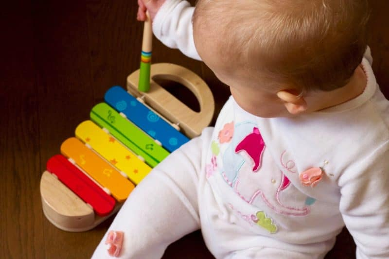 Baby plays with colored rainbow xylophone made of wood and metal